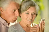 Happy elderly couple with a mobile phone — Stock Photo