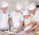 An elderly couple and their grandson knead the dough for the pie together — Stock Photo