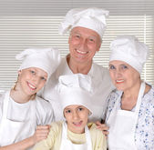 Older couple and their grandchildren knead the dough for biscuits together — Stock Photo