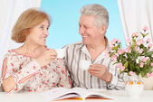 Cute old couple at breakfast at table — Stock Photo