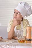 Young boy in a chef's hat knead dough for cookies — Stock Photo
