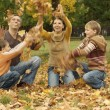 Family throw autumn leaves — Stock Photo