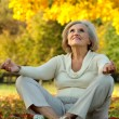 Old woman sitting in the autumn park — Stock Photo