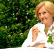Beautiful Caucasielderly womsitting with flower — Stock Photo #29824885