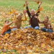 Elderly couple and children throwing leaves — Stock Photo