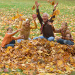 Elderly couple and children throwing leaves — Stock Photo #29825433