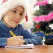 Pretty Caucasian teenager in a santa hat draws  — Stock Photo