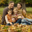 Family sitting in a autumn park — Stock Photo