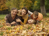 Happy family lying in autumn park — Stock Photo