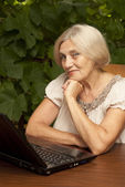 Glad older woman sitting on the veranda — Stock Photo