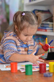 Child draws paints at the table — Stock Photo