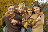 Family relaxing in a beautiful autumn park — Stock Photo