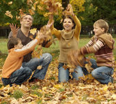 Beautiful family throw autumn leaves — Stock Photo