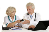 Elderly doctors with a laptop — Stock Photo