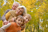 Elderly couple and boys resting in autumn — Stock Photo