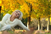 Old woman sitting on the autumn leaves — Stock Photo