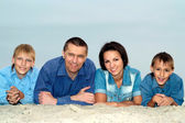 Family lying on light sand — Stock Photo