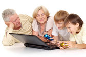 Grandchildren with their amusing granddad and granny — Stock Photo
