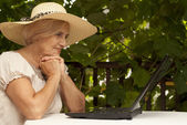 Playful older woman sitting on the veranda — Stock Photo