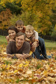 Family lying in autumn park — Stock Photo