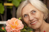 Attractive older woman sitting on the veranda — Stock Photo