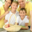 Happy family with a basket of fruit — Stock Photo