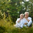 The old couple sitting in grass and eating apples — Stock Photo