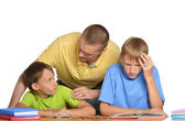 Father helping his sons with their homework — Stok fotoğraf