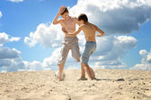 Two boys playing football on a sand — Stock Photo