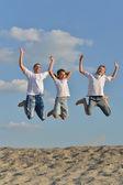 Happy family jumping outdoors — Stock Photo