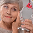 Portrait of a happy aged woman with mirror — Stock Photo