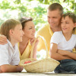 Happy family with a basket of fruit — Stockfoto