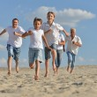 Happy family running on a beach — Stock Photo