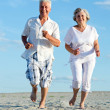 Stock Photo: Old couple running on beach