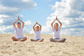 Happy family sitting on a sand and doing yoga — Stock Photo
