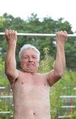 Elderly man on horizontal bar — Stock Photo