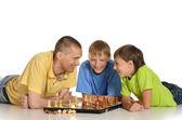 Padre y dos hijos jugando al ajedrez — Foto de Stock