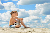 Two boys sitting on the sand with a soccer ball — Stockfoto