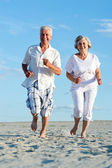 Old couple running on a beach — Stock Photo