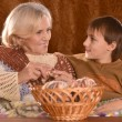 Senior woman knitting in armchair with her grandson — Stock Photo