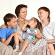 Happy family resting at home on the couch together — Stock Photo