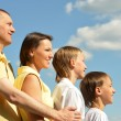 Family of four against blue sky — Stock Photo