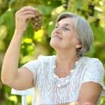 Senior lady eating fruits outdoors — Stock Photo #30478841