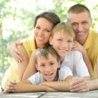 Happy family at wooden table — Stock Photo