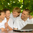 Family with laptop in nature — Stock Photo