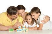 Rodina hrát s kostkami izolovaných na bílém — Stock fotografie