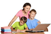Kids doing homework with mother — Stock Photo