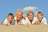 Kids on a beach with grandparents — Stock Photo