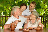 Family drinking tea outdoors — Stock Photo