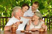Family drinking tea outdoors — Stock Photo
